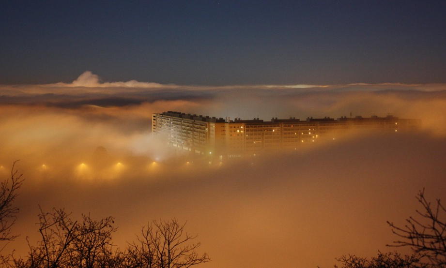 a condominium building covered in night fog
